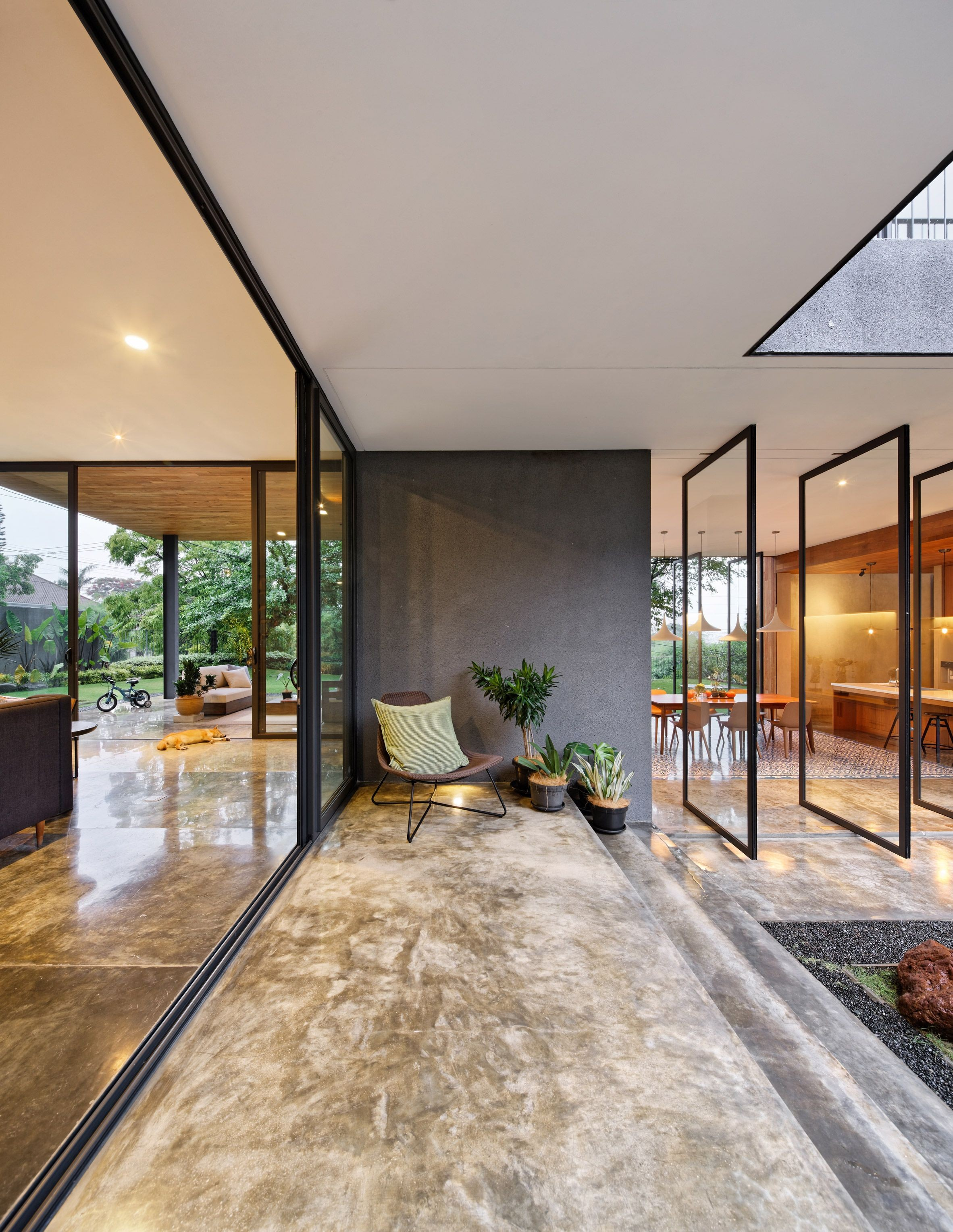 The entrance leads directly into a kitchen and dining area lined on both sides by glass doors that pivot open to allow air to waft through the space
