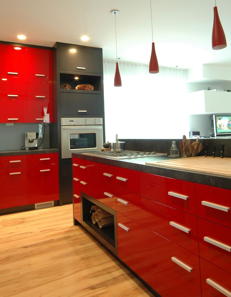 This modern style kitchen blends graffiti black and high gloss red finish with sleek doors handles and a plimentary stone top